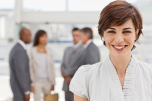 Closeup portrait of happy businesswoman with colleagues in the background